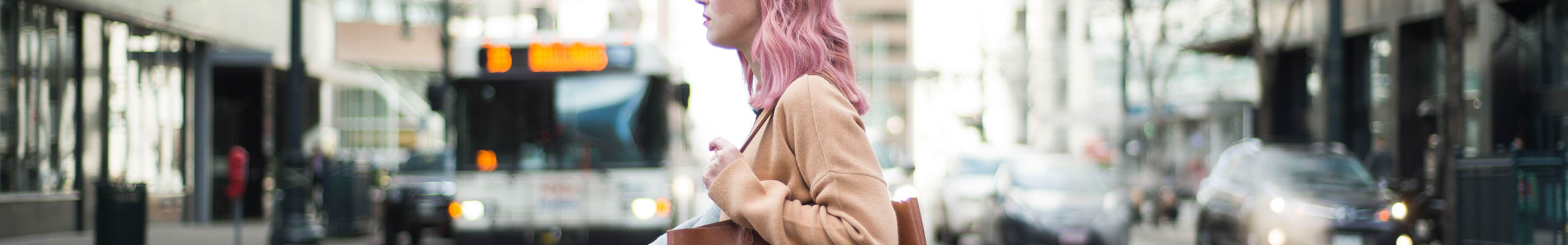 person with pink hair walking in a cityscape