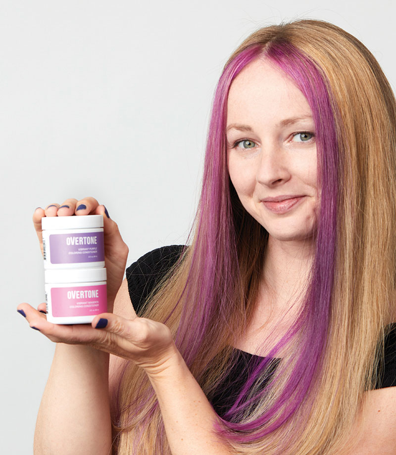 Person with money piece hair and holding two sample size coloring conditioners.
