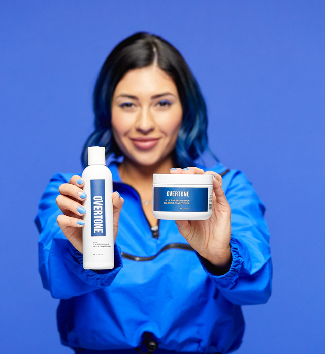 person holding a blue for brown hair coloring conditioner and daily conditioner