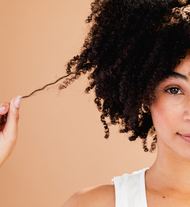 person with curly hair pulling a tendril