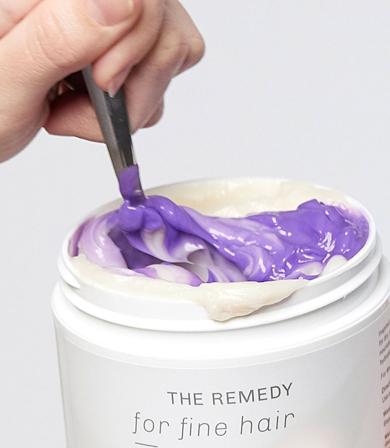 A person's hand mixing purple conditioner with the remedy conditioner