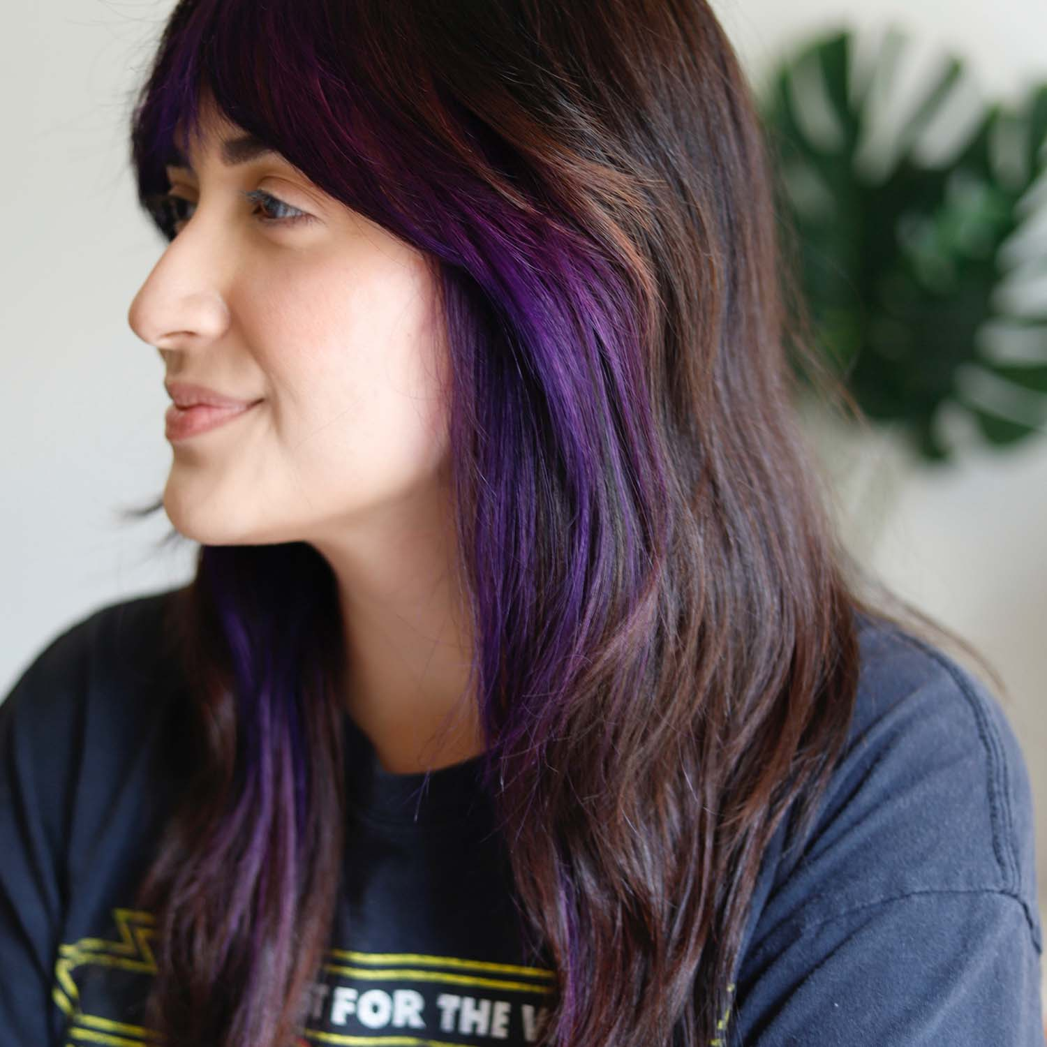 Person with brown hair and purple money piece in their hair.