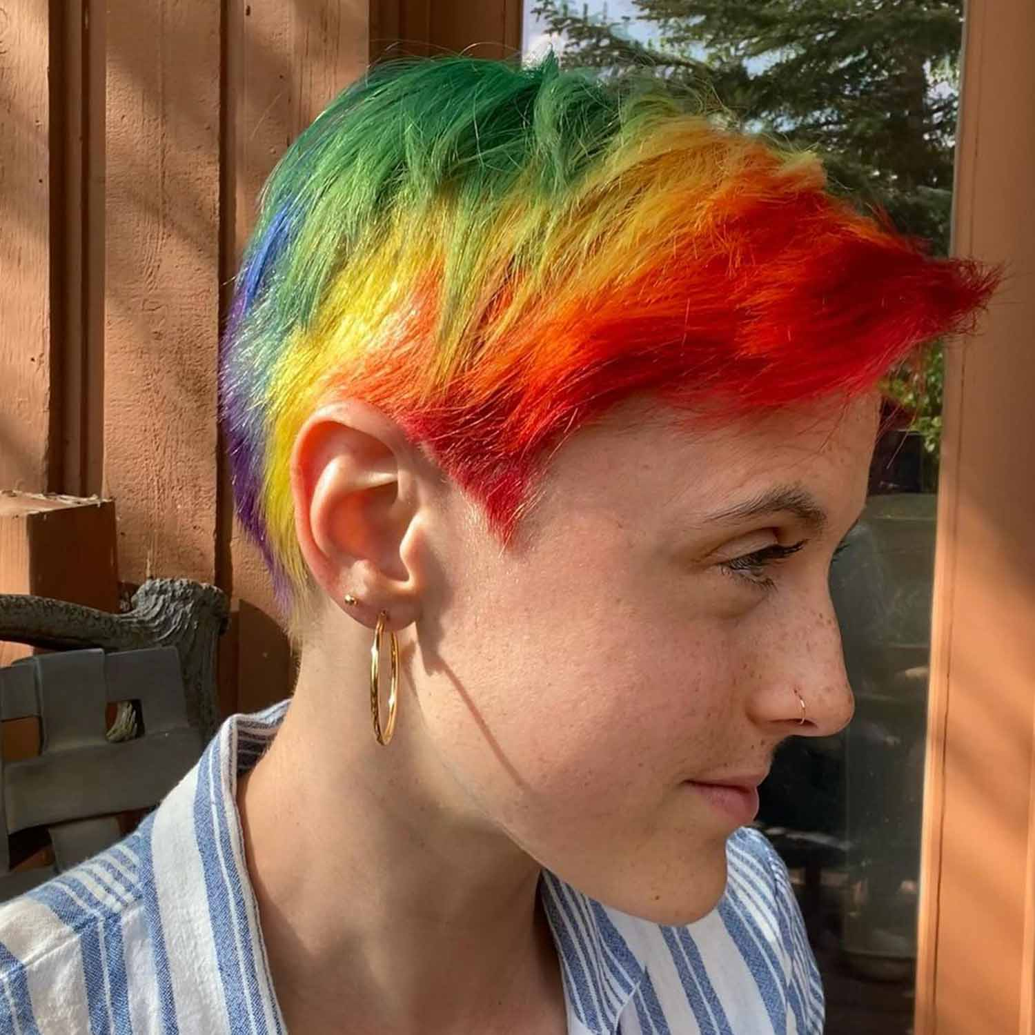 Person with a pixie cut and rainbow streaks in their hair.